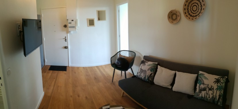 Le salon qui donne sur la cuisine, une chambre et l'entrée